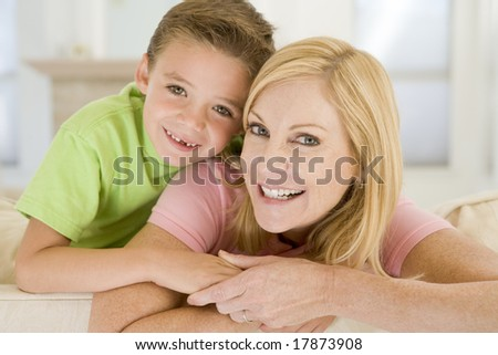 Woman and young boy sitting in living room smiling