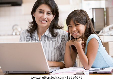 Woman and young girl in kitchen with laptop and paperwork smiling
