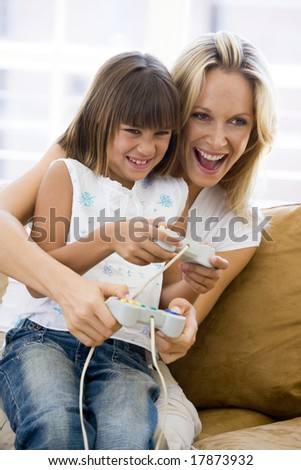 Woman and young girl in living room with video game controllers smiling - stock photo
