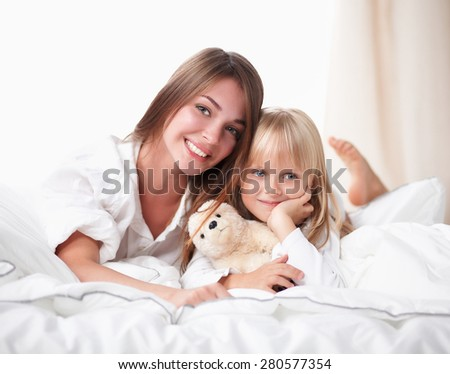 Woman and young girl lying in bed smiling. - stock photo