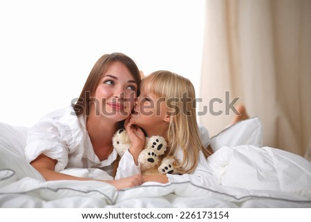 Woman and young girl lying in bed smiling, isolated - stock photo