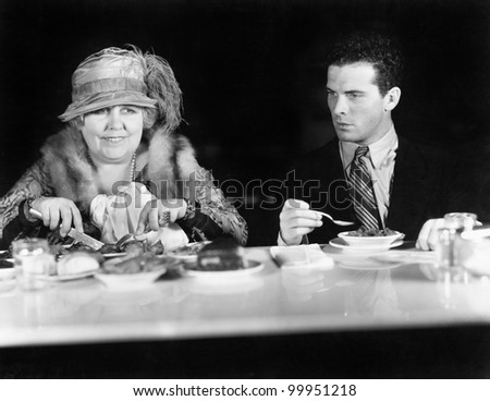 Woman and young man sitting at a coffee counter - stock photo