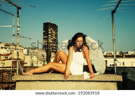 woman angel on building roof, summer day, Belgrade, Serbia - stock photo