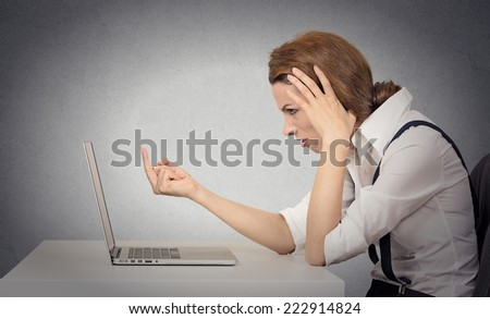 Woman angry frustrated annoyed at computer. Problems with hardware, software, internet shopping. Negative human face expressions, emotions, feelings, body language, bad attitude, life perception - stock photo