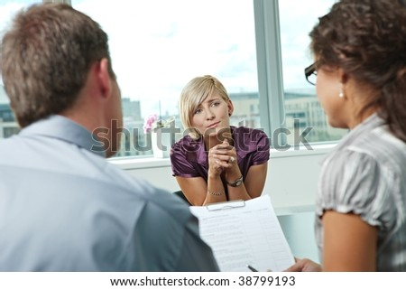 Woman applicant craving for job during job interview. Over the shoulder view.