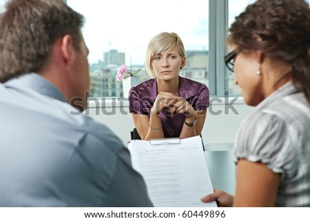 Woman applicant worrying during job interview. Over the shoulder view.