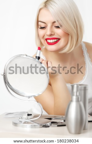 Woman applies red lipstick  Red Lips and Blond Hair. Daily Make-up - stock photo