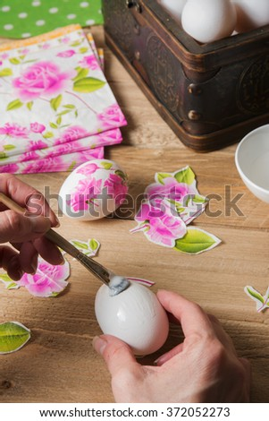 woman apply  glue on colored Easter egg, with the technique of decoupage