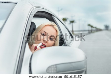 Woman apply rose lipstick looking in car mirror