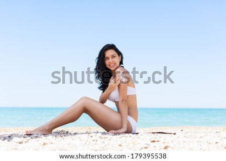 woman apply sunscreen protection lotion hand on arm shoulder, young girl smile with tanned body, sitting on summer beach travel ocean vacation, female applying suntan cream skin care sun protect - stock photo