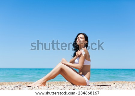 woman apply sunscreen protection lotion hand on arm shoulder, young girl smile with tanned body, sitting on summer beach travel ocean vacation, female applying suntan cream skin care sun protect