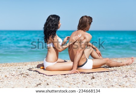woman apply sunscreen protection lotion on man back tanned body, summer beach travel ocean vacation, couple smile applying skin care sun protect