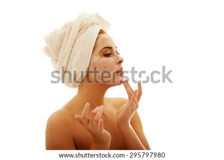 Woman applying a cream on her face.
