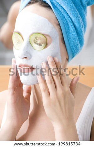 Woman applying beauty mask, close-up