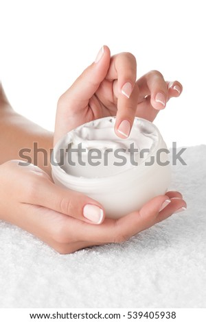 Woman applying body cream. Close-up composition of hands with white jar isolated on white background. Vertical composition.