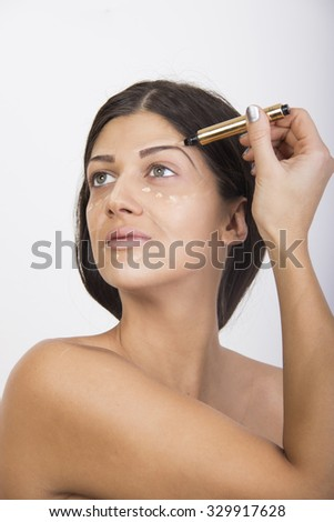 woman applying concealer on face