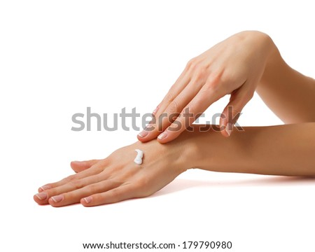 Woman applying cosmetic cream on her beautiful hands - stock photo