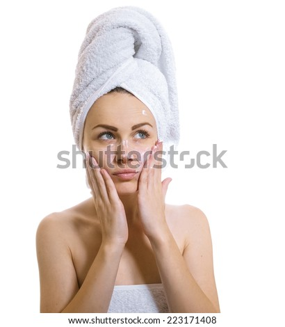Woman applying cosmetic cream treatment on her face on white.Female after bathing,isolated on white