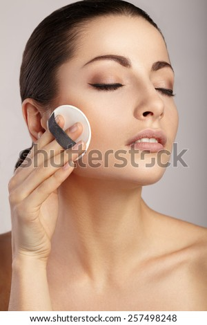 Woman applying cosmetic sponge on her face - stock photo