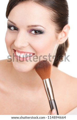 Woman applying cosmetics to her face with the help of cosmetic brush, isolated on white - stock photo
