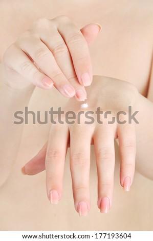 Woman applying cream on hand - stock photo