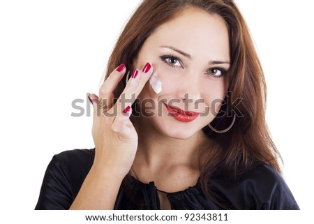 Woman applying cream on her face isolated on white - stock photo