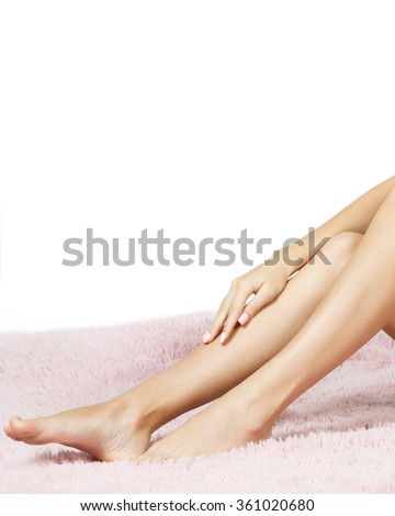Woman applying cream on her leg while sitting on a blanket
