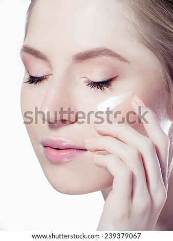 woman applying cream on the face close eyes
