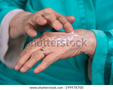 Woman applying cream to her hands - stock photo