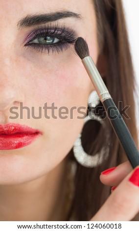 Woman applying eye shadow while looking at camera - stock photo