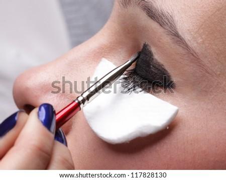 Woman applying eyeshadow using professional makeup brush - stock photo