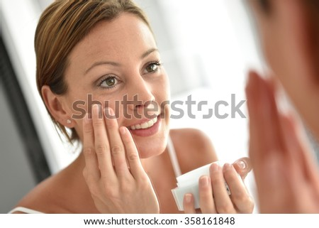 Woman applying facial cream on her face - stock photo