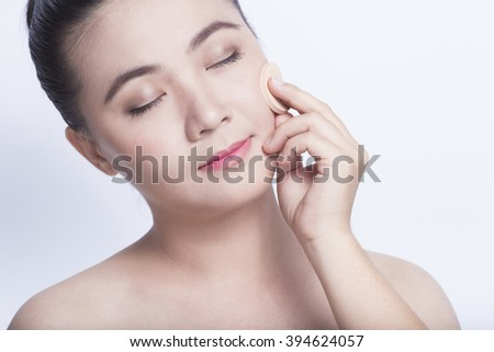 Woman applying foundation with sponge