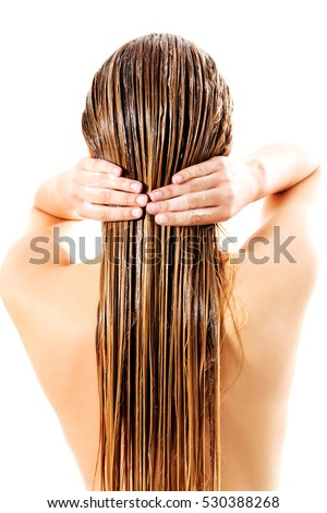 Woman applying hair conditioner. Isolated on white.
