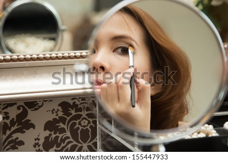 Woman applying her eyeshadow in front of the mirror