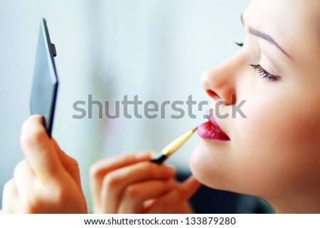 woman applying her make-up in the mirror - stock photo