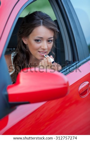 Woman applying lipstick using the car's mirror - stock photo