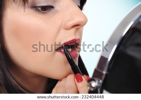 woman applying lipstick with a brush on lips - stock photo