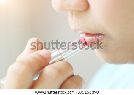 woman applying make up by lipstick. - stock photo
