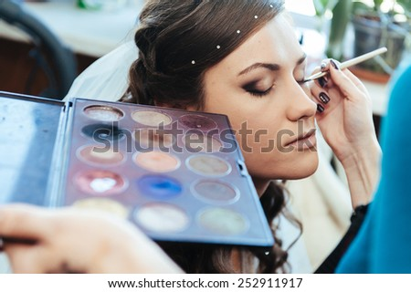 Woman applying make up for a bride in her wedding day near mirror. Closeup of a makeup artist applying makeup