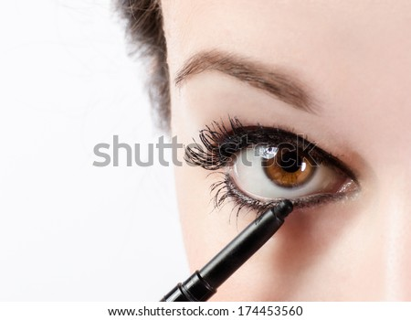 Woman applying make-up with eye pencil - stock photo