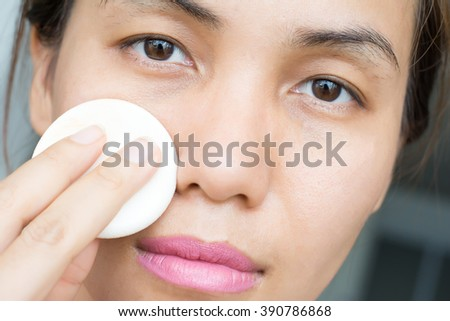 woman applying make up with powder puff