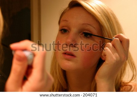 woman applying makeup in front of mirror