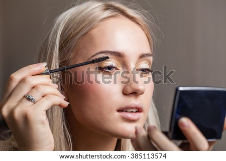 woman applying makeup using make up brush with mirror - stock photo