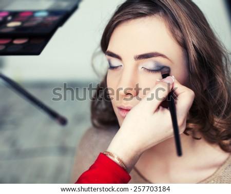 Woman applying makeup with brush - stock photo
