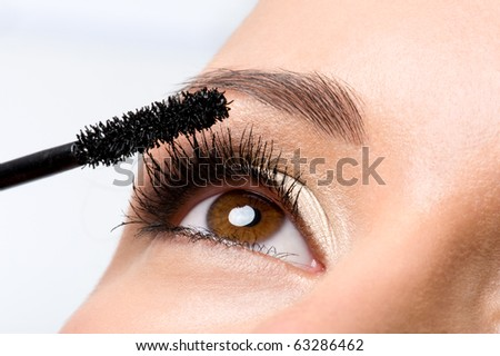 Woman applying mascara on her eyelashes - macro shot - stock photo