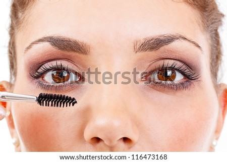 Woman applying mascara on her long eyelashes - stock photo
