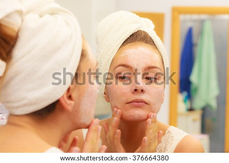 Woman applying mask moisturizing skin cream on face looking in bathroom mirror. Girl taking care of her complexion layering moisturizer. Skincare spa treatment.  - stock photo