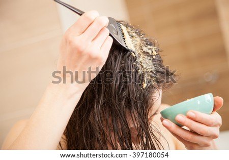 Woman applying mask to hair roots to make them grow stronger and faster and to prevent hairloss - stock photo