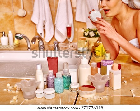 Woman applying moisturizer at bathroom. Cosmetic on foreground. - stock photo
